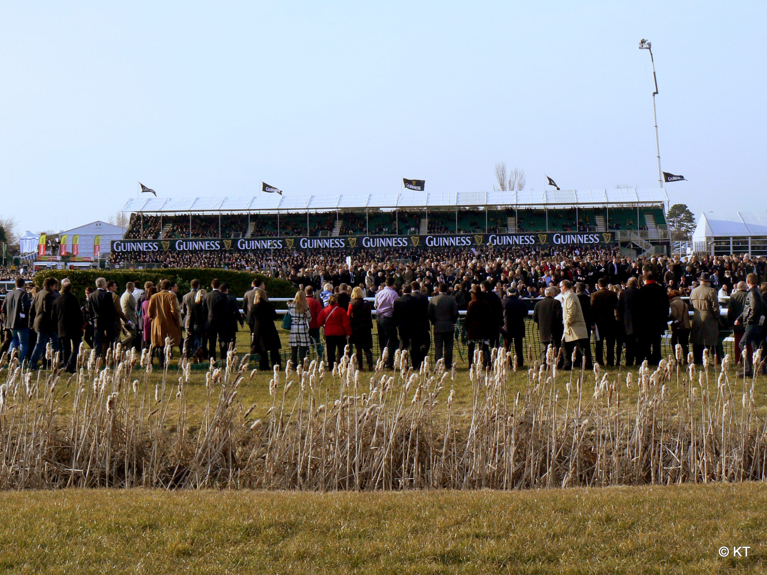 Crowds watch from the Cross County Course at Cheltenham Racecourse in Cheltenham, Gloucestershire, England